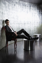Stylish Man sitting, legs on ottoman, in metal room, side view