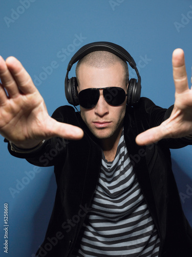 Man wearing headphones in studio view through hands