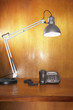 Desk Lamp and Phone on Wooden Desk