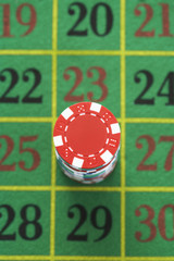 Stack of gambling chips on roulette table, view from above