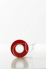 Roll of red tape in dispenser