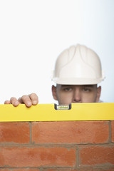 Man in hard hat using level to check brick wall, high section