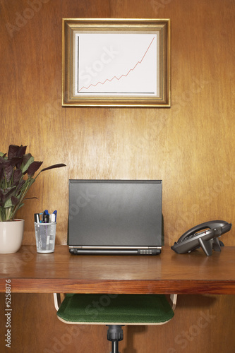 Laptop and other items on desk, framed graph above desk