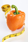 Peppers with a tape measure on a reflective tabletop  poster
