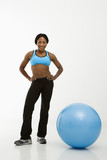Woman standing with exercise ball. poster