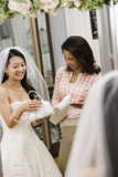 Woman helping bride with handbags. poster