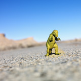Toy dinosaur in road. poster
