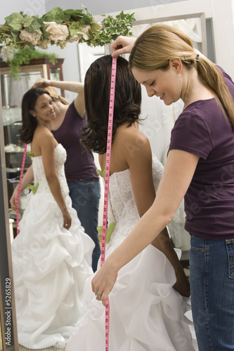 Seamstress measuring bride.