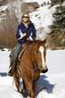 Woman horseback riding in snow.