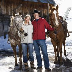 Couple holding horses.