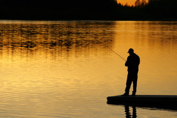 A silhouette of a fisherman as the sunset on lower.