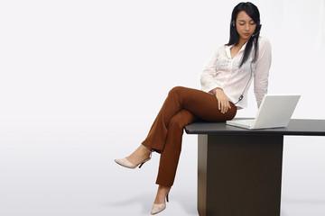 Mujer sentada en escritorio con laptop