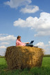 Young man with laptop over country view