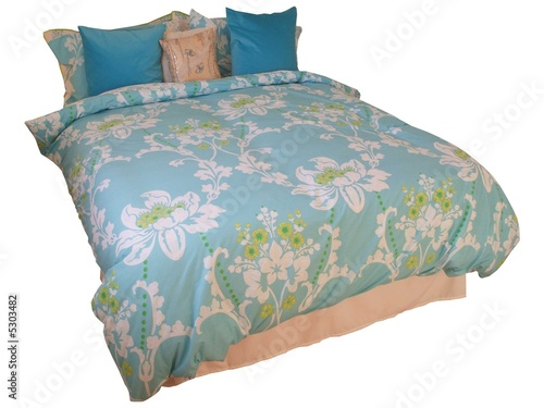 A Double Bed with a Colourful Quilt Cover.