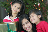 Three happy sisters holding their Christmas presents poster