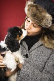 Woman wearing fur hat kissing King Charles Spaniel. poster