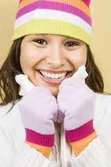 Young woman wearing winter hat and gloves and smiling.