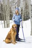 Female skier standing on ski slope with Golden Retriever. poster