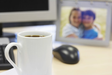 Coffee mug on desk by computer and family photo, close up of mug