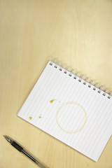 Coffee Ring on Notebook on desk, overhead view
