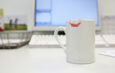 Lipstick Print on Coffee mug by computer on desk, close up