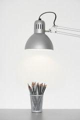 Angle poise lamp shining on cup of pencils