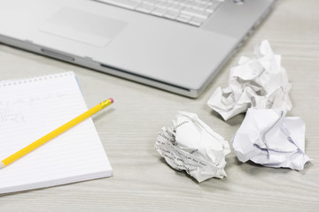 Crumpled paper and notebook on desk by laptop, close up