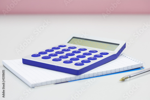 Calculator notebook and pen on table, close up