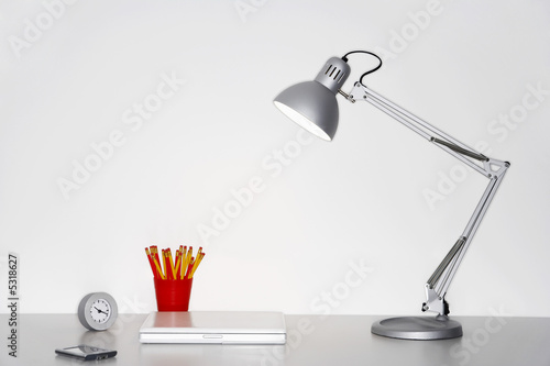 Angle poise lamp, laptop, clock, pencils and PDA on desk