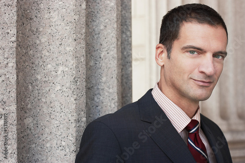 Businessman by outdoor column, portrait