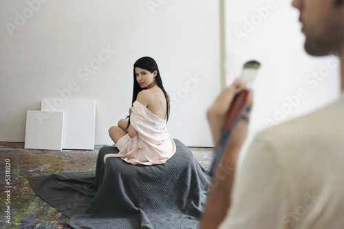 Female model posing for artist in studio, back view