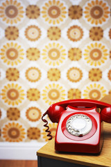 Old fashioned red telephone on table in front of flowery wallpaper