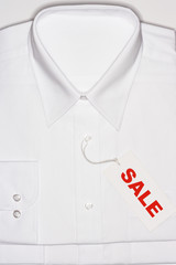 Folded white shirt with 'sale' tag