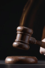 Gavel hitting base, black background