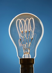 Transparent light bulb against blue background in studio