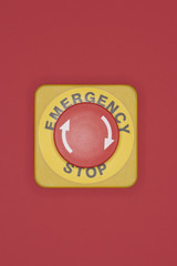 Emergency stop button on red background