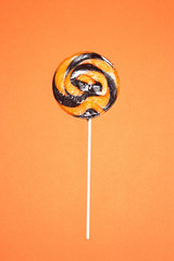 Black and orange lollypop on orange background