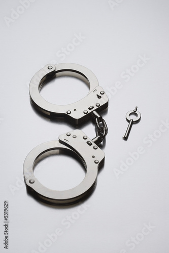 Handcuffs and key on white background in studio