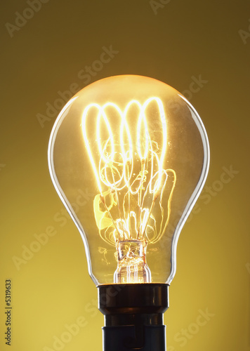 Illuminated light bulb against yellow background in studio