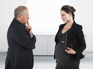 Boss talking to pregnant businesswoman, half length