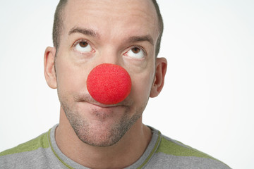 Man Wearing Clown Nose, looking upwards in disgust