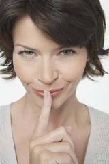 Woman with Finger on Lips, grinning mischievously, close-up