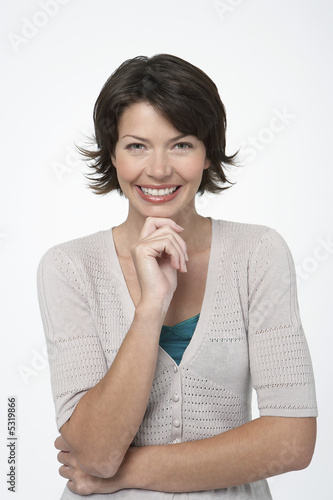 Smiling Woman standing, hand on chin