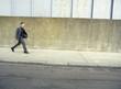 Teenager in suit walking on street, side view