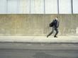 Teenager in suit running on street, looking back