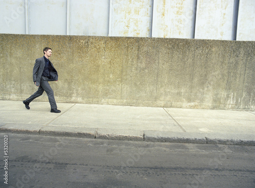 Teenager in suit walking on street, side view
