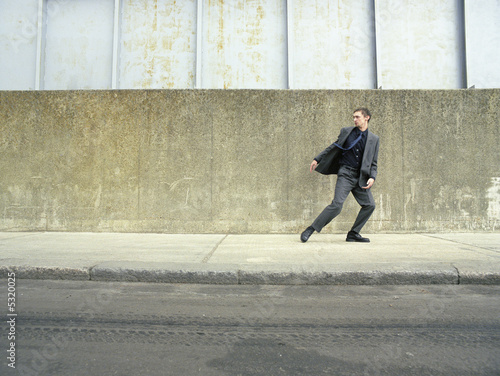 Teenager in suit running on street, looking back