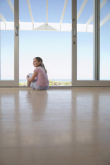 Girl sitting on floor in doorway, smiling