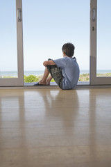 Boy sitting on floor in doorway looking at view