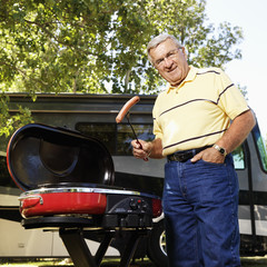 Senior man grilling by RV.